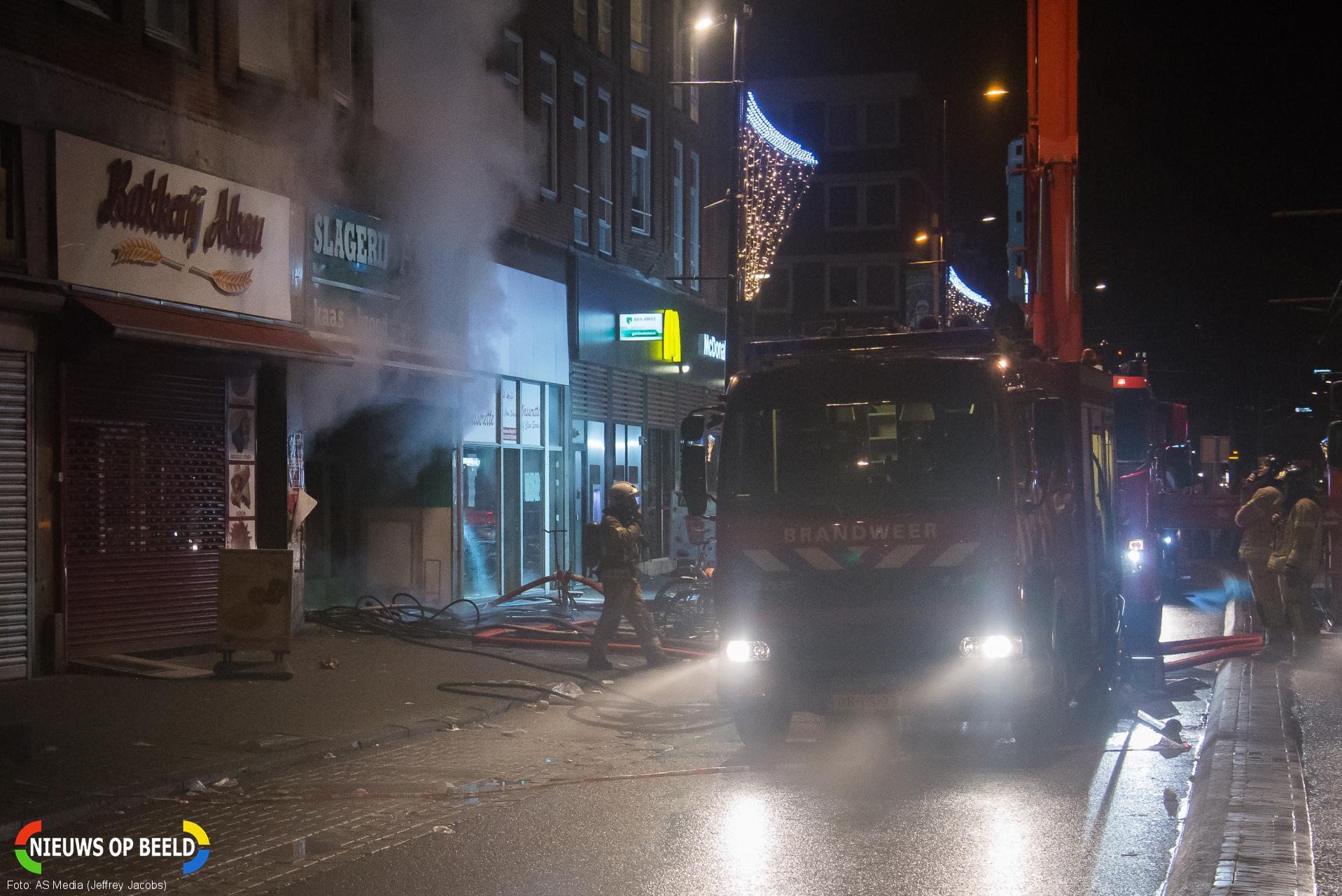 Brandweer redt bewoners uit huizen en van het dak na felle winkelbrand Schiedamseweg Rotterdam
