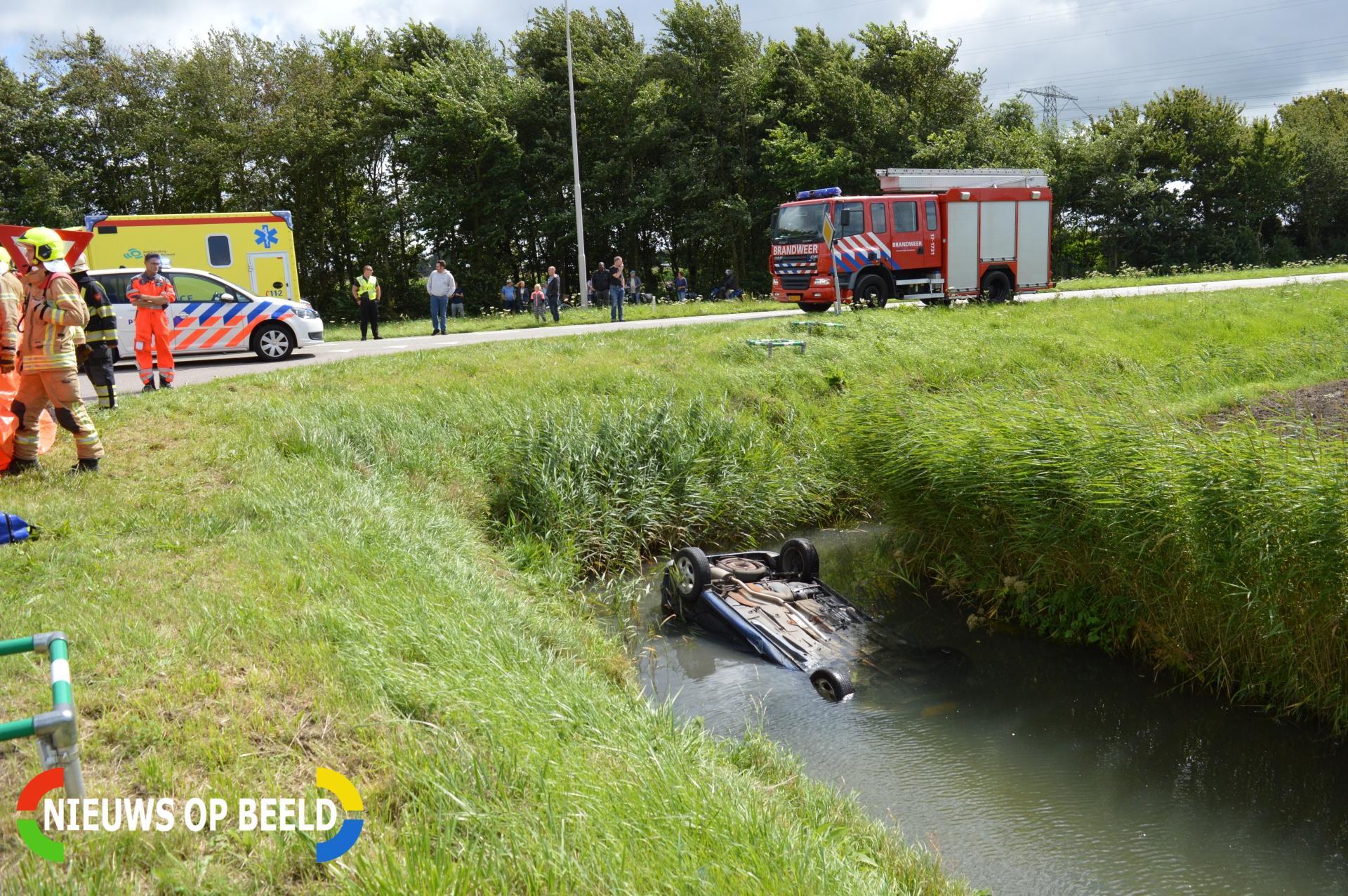 Auto op zijn kop in de sloot Schrijversdijk Oostvoorne