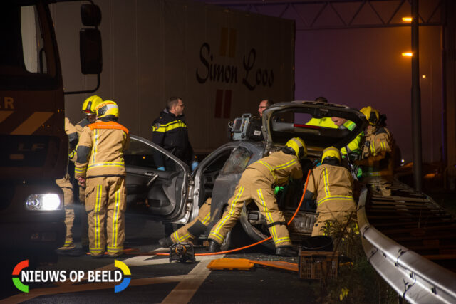 De brandweer is bezig met het bevrijden van een inzittende uit een betrokken auto