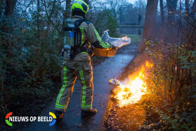 Brandweerman blust het vuur met een bak water