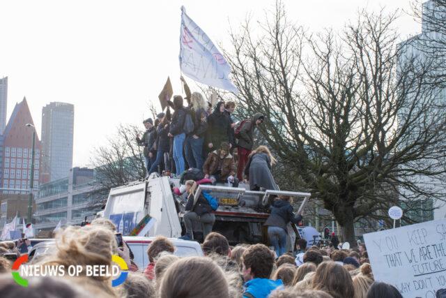 Een tiental personen zijn op een vuilniswagen geklommen die vast staat in de demonstrerende massa