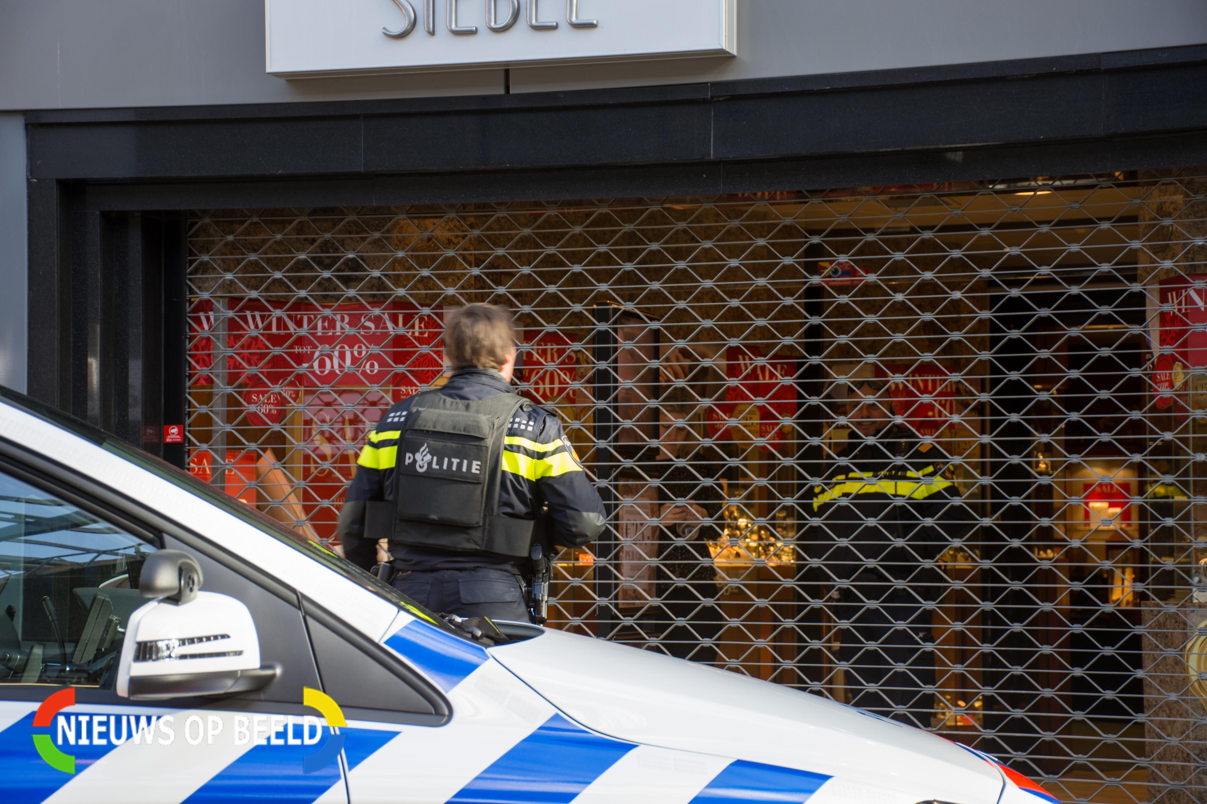 Een agente staat in kogelwerend vest voor de juwelier
