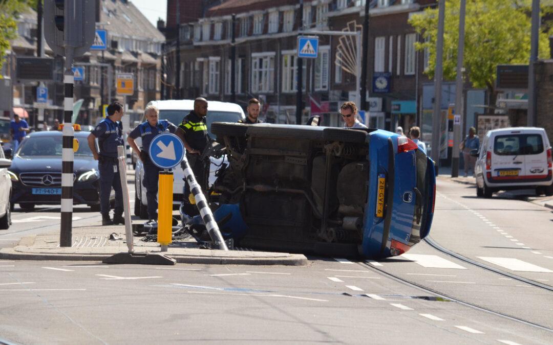 Auto crasht en belandt op zijn kant op kruising Rozenlaan-Kleiweg in Rotterdam